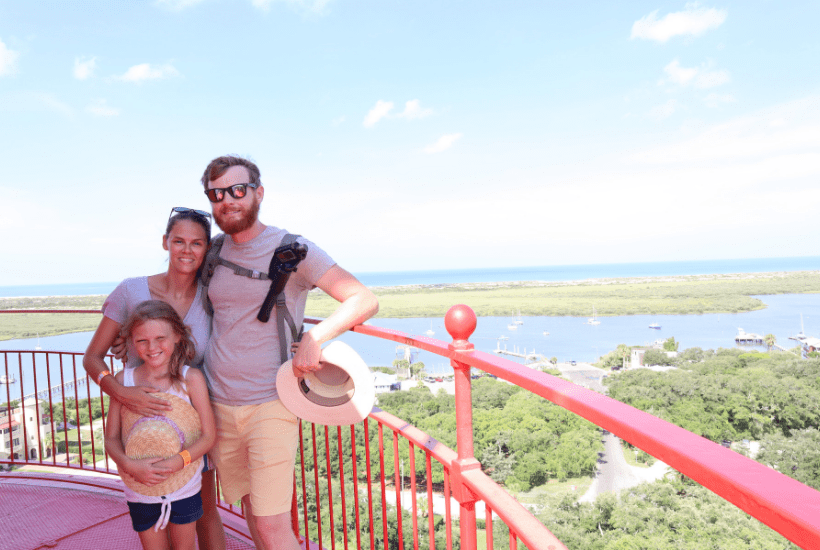family of 3 posing for picture at the top of st augustine lighthouse